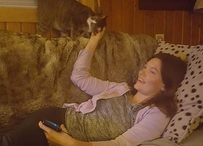 Woman lying on couch pets cat standing above her.