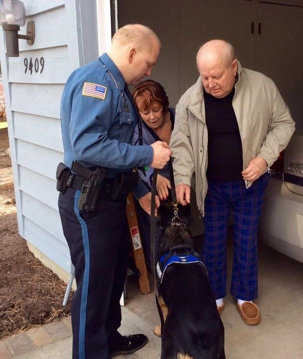 Officer with German shepherd as older man and woman pets the dog